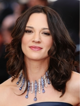 Get Asia Argento's wavy hairstyle by blow-drying with a round brush for a bit of volume and twisting the ends out in soft waves.  Smooth crown with a glossifier.