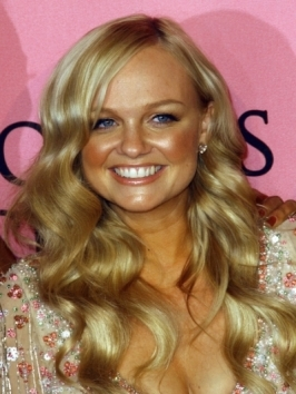 Volume around the crown, sweeping fringe and soft end waves play up Emma Bunton's long locks.  To balance out a round face shape, make sure to keep volume and movement below the chin-level.