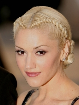 Crown height and an ultra-sleek finish take Gwen Stefani's voluminous hairstyle to a serious party 'do! Pack roots with body with teasing, then direct hair to fall right around the back of the head. Mist generously with strong hold hairspray to finish the look!
