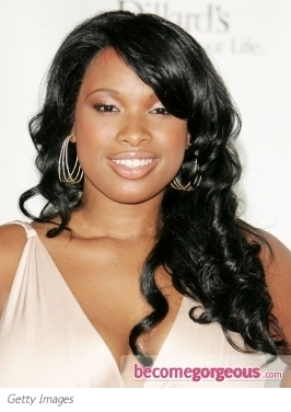 Jennifer Hudson goes for a face-framing haircut with lots of layers and full-on bangs. Here, she wears her 'do with lots of curly texture with a shiny finish.