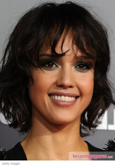 Jessica Alba puts a spin on the basic smokey eye makeup by adding a splash of color with a pretty shimmery finish. False lashes, a peachy blush and pink/nude lip color complete the look.