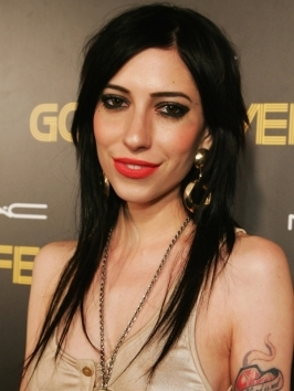 The Veronica's Jessica Origliasso edges up her long blonde bob with long lash-tickling bangs and a poker-straight finish. The progressive layers move from longer up front to shorter toward the back for a slightly angled line.