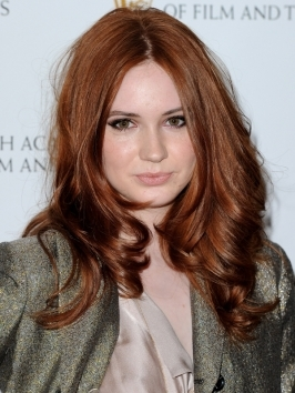 Karen Gillan's warm red hair color flicker with depth and dimension and gets its kick from an intense base and subtle swirls of golden-hued highlights. Her lush end-curls were created by wrapping sections around a wide barrel curling iron forming plump, defined curls.