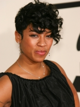 Keisha Cole is wearing a highly texturized short curly hairstyle. Tapering on the sides prevents top bulky layers from overpowering her face.