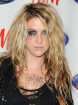 Ke$ha works her signature tousled wavy texture with a middle parting and a hint of volume. To style, work in texturizer and rough dry with your fingers. Define ends with a large barrel curling iron from mid-lengths down.