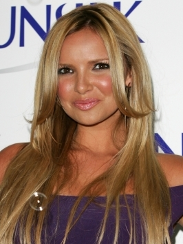 Girls Aloud's Nadine Coyle's glossy locks start with a beautiful hair color and polished surface. Her style is created with a center part and directing layers in toward the collarbone.