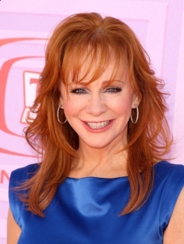Reba McEntire pairs her spicy copper hair color with all over layers and soft whispy bangs.