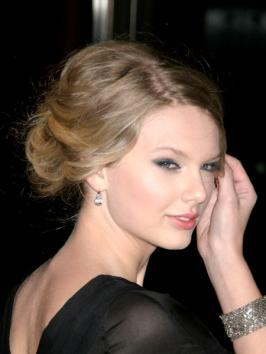 Taylor Swift pairs her lash-tickling bangs with a classy chignon. Her long locks have been twisted on the sides then rolled up and secured at the nape.