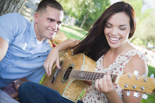 Guy Listening To Girl Playing The Guitar